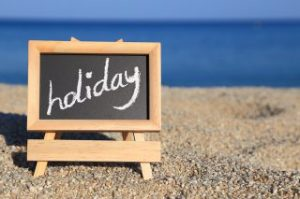 Blackboard with holiday text on the beach